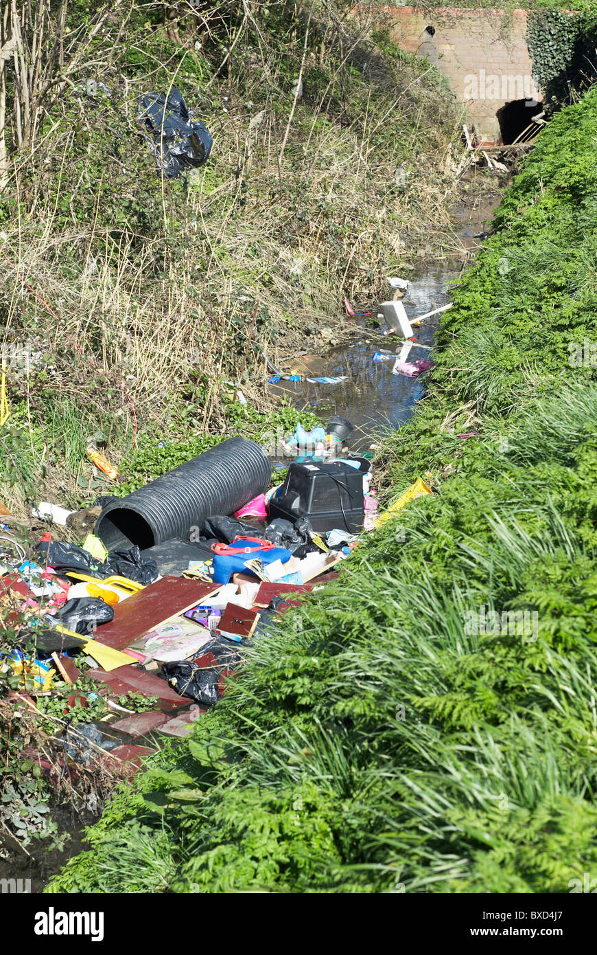 Fly-tipping in a stream Kings Lynn Norfolk UK - Stock Image