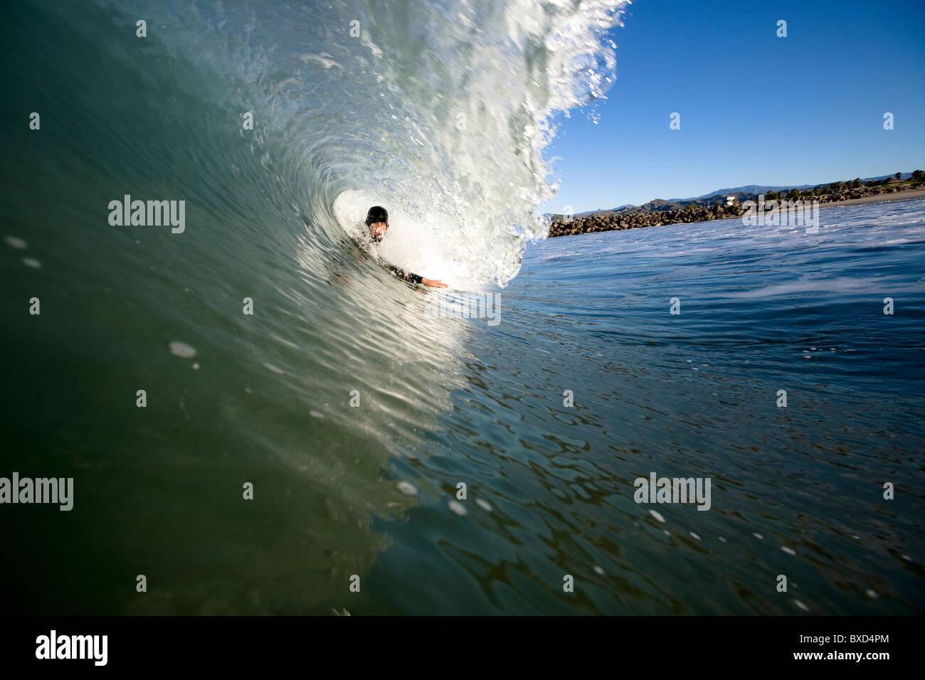 A male bodysurfer gets barrel. - Stock Image