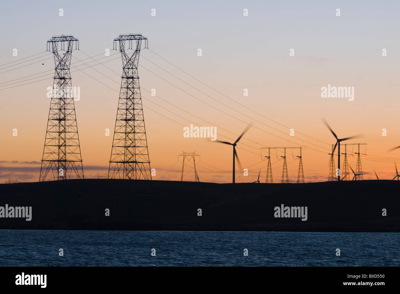 Wind turbines and power transmission lines at sunset near San Francisco - Stock Image
