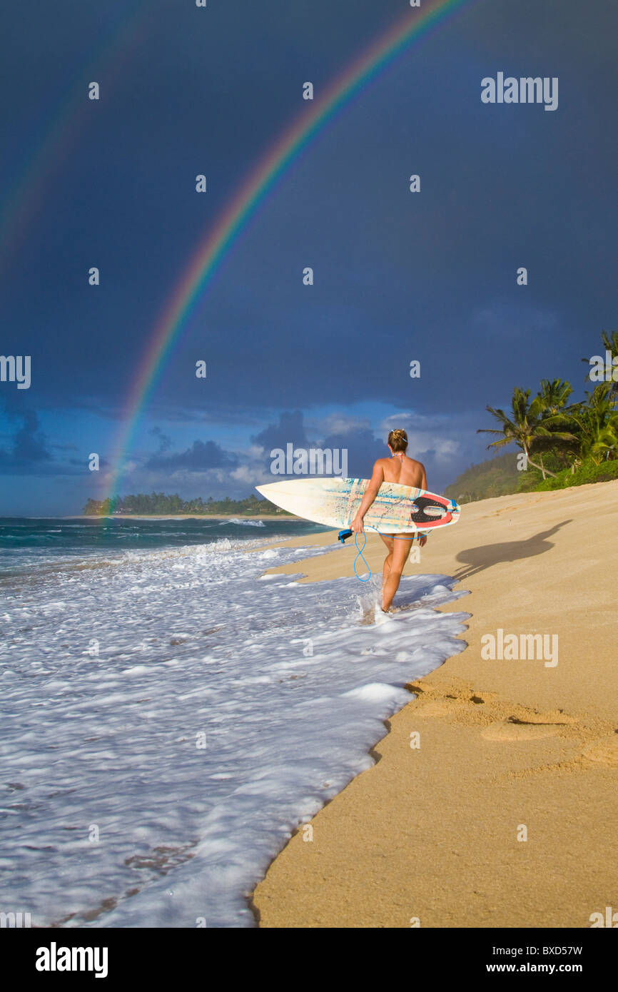 An amazing rainbow over Rocky Point, as a surfer girl walks along the beach, on the north shore of Oahu, Hawaii. - Stock Image