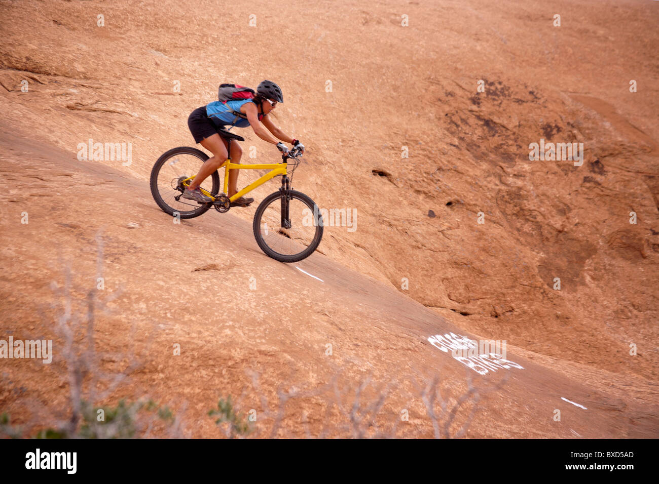 A woman mountain bikes one of the Slick Rock routes in Moab Utah. - Stock Image