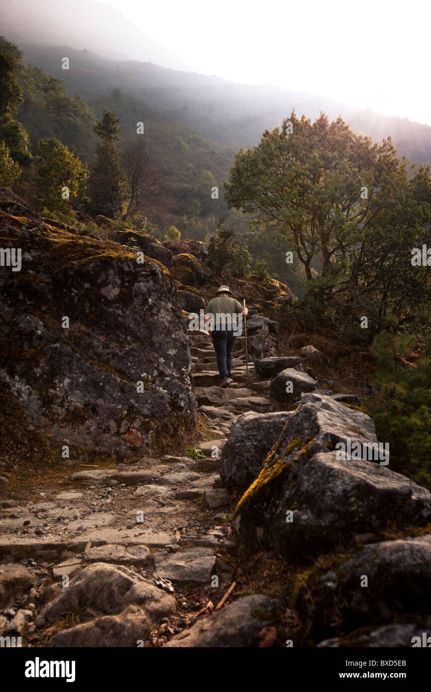 An unladen male trekker ascends a stone staircase to Lukla, Nepal. Stock Photo