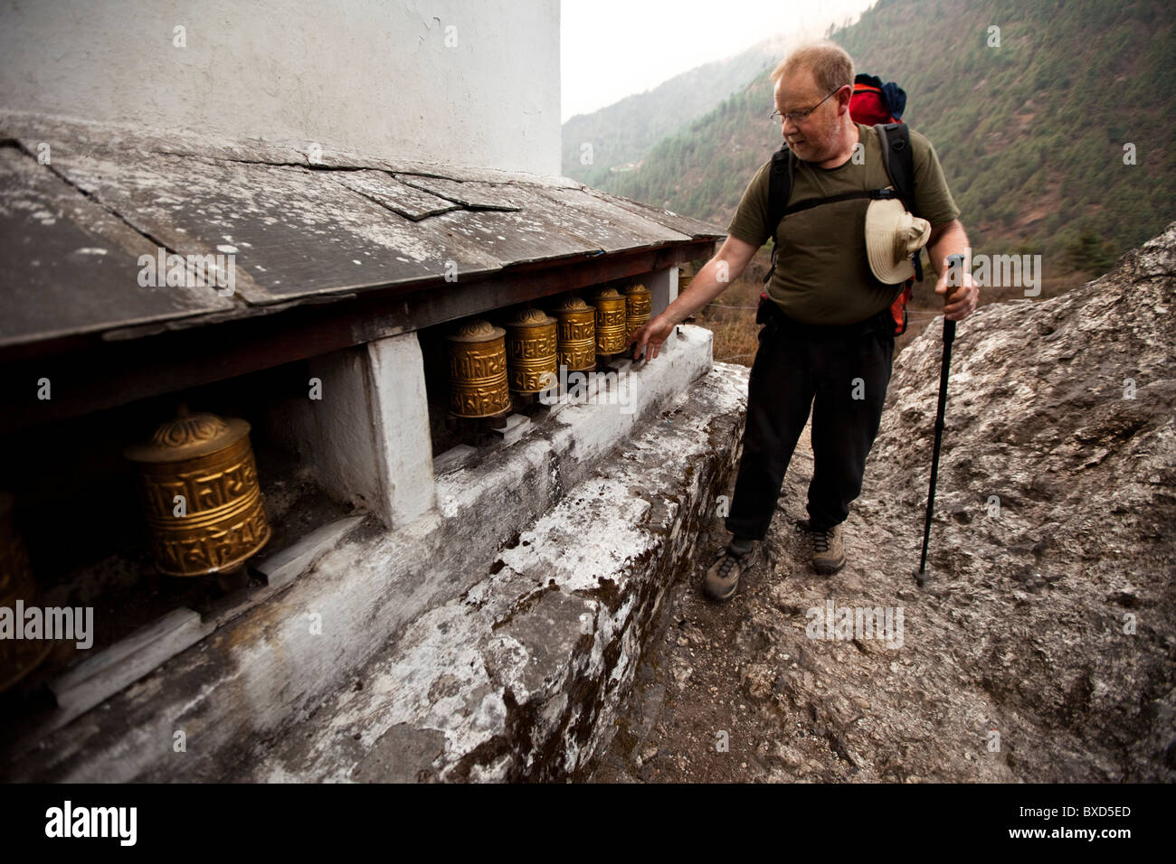 A male trekker spins prayer wheels while navigating the trail out of Lukla, Nepal. - Stock Image