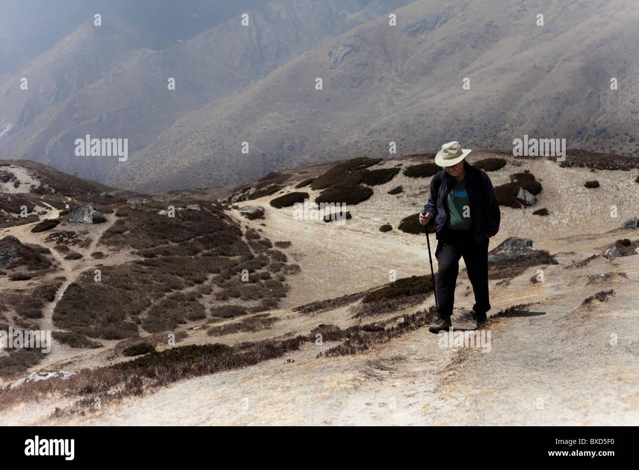 An unladen, male trekker walks to Amadablam base camp. - Stock Image