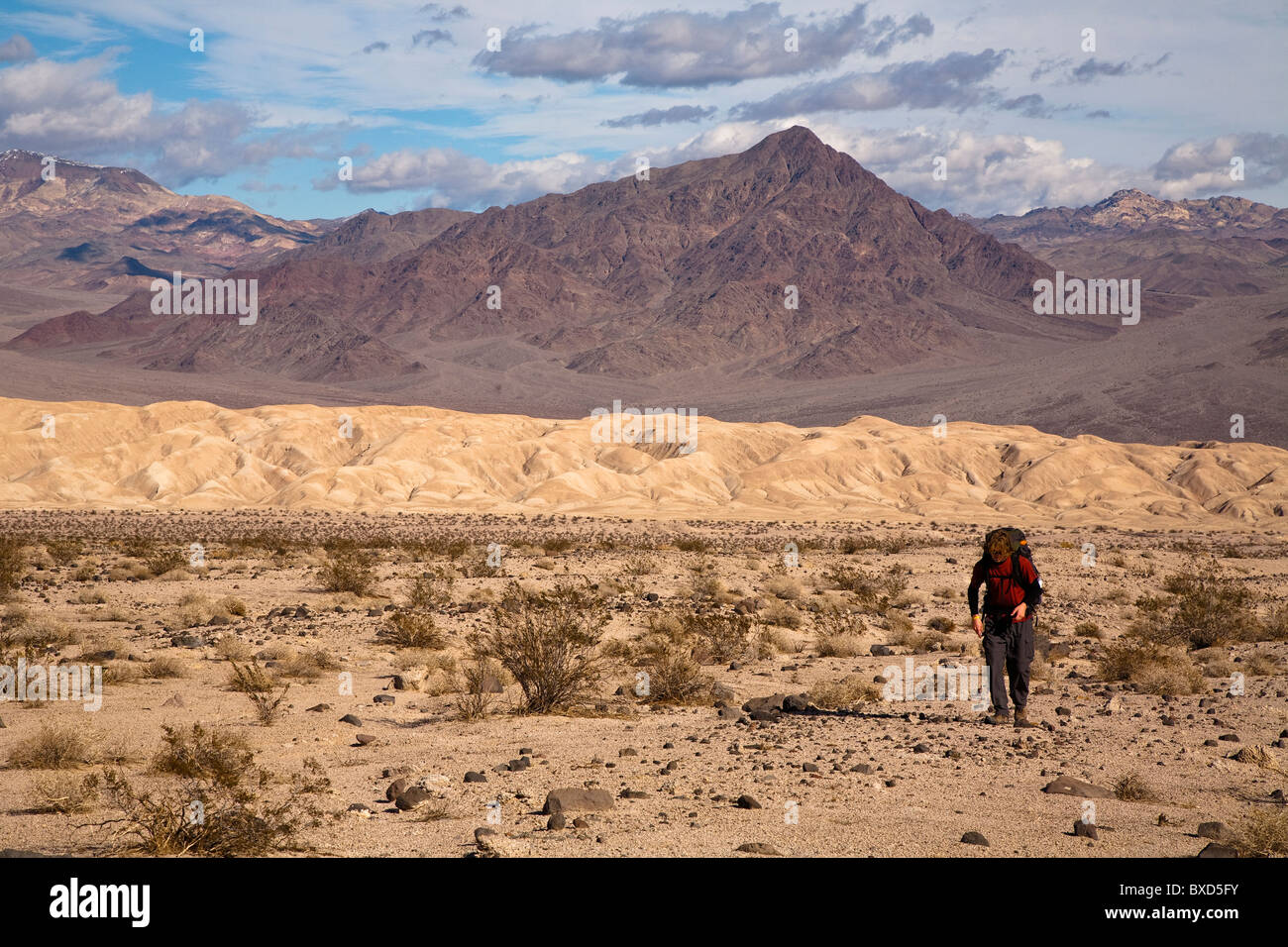 A young man backpacks through the Confidence Hills in Death Valley Nation Park, California. - Stock Image