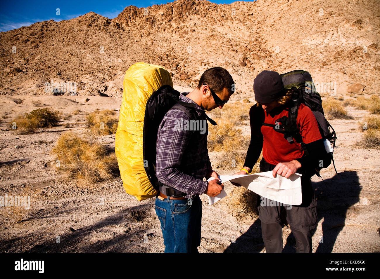 Two male hikers look over a map while backpacking through the Confidence Hills in Death Valley Nation Park, California. - Stock Image