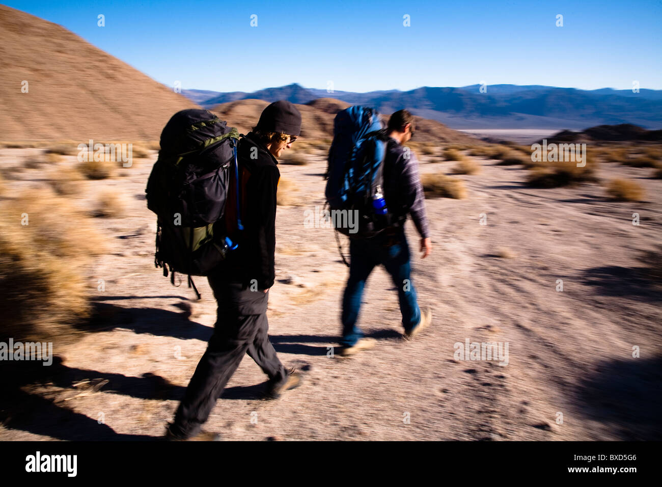 A pair of young male hikers backpack through Death Valley's Confidence Hills, California. - Stock Image