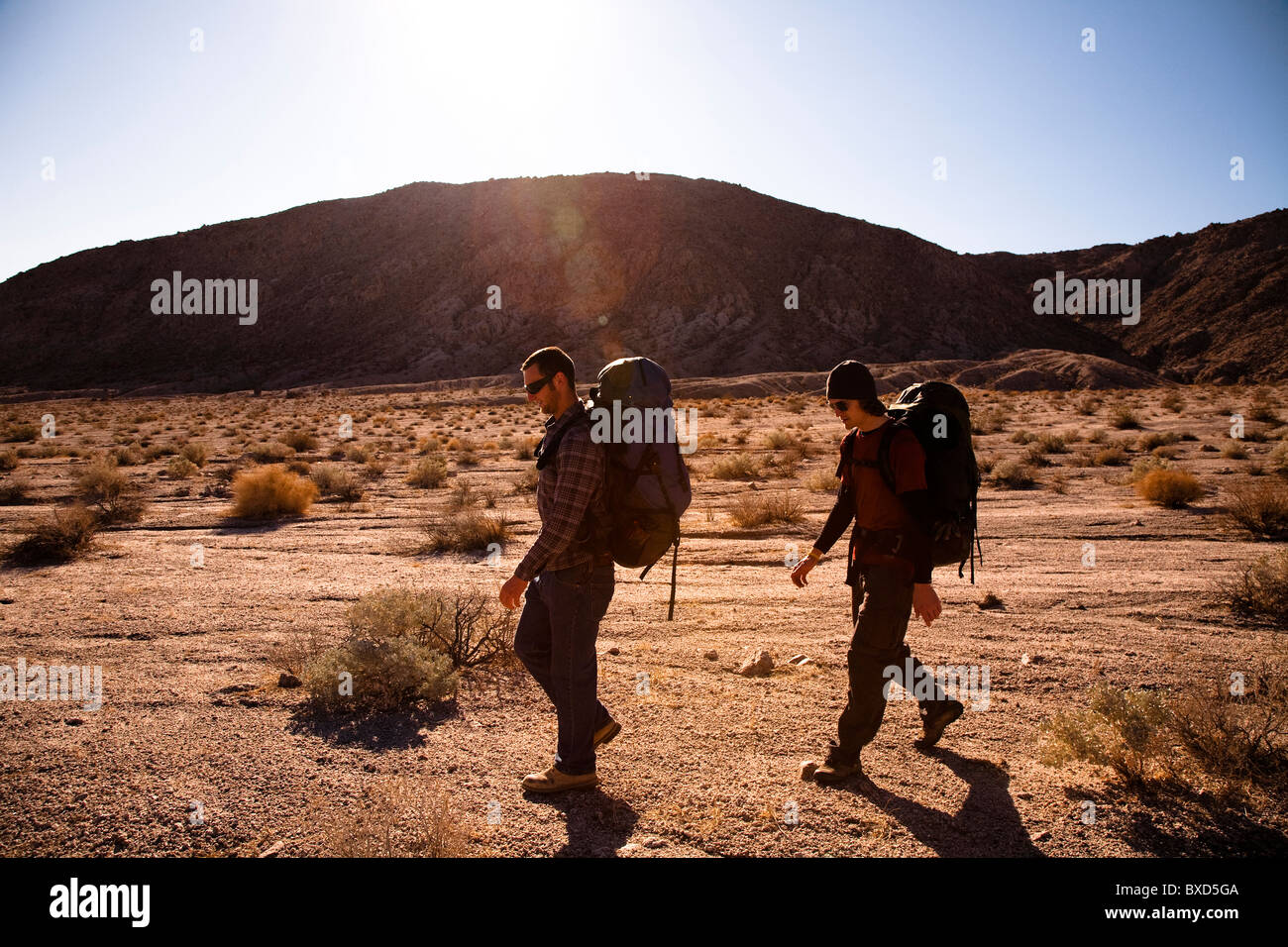During the heat of the midday sun, two male hikers backpack through Death Valley's Confidence Hills, California. - Stock Image