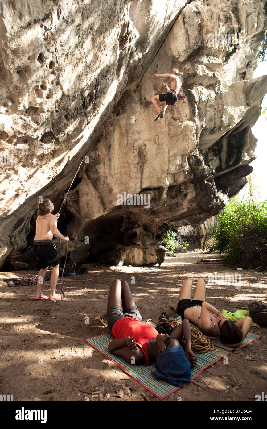 A caucasian male climber falls on lead while belayer catches and two women watch. - Stock Image