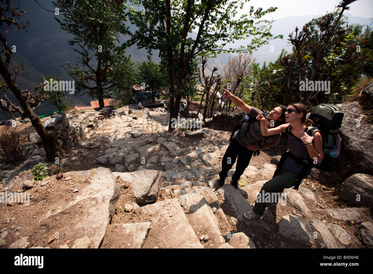 Two trekkers looking and pointing uphill in Nepal. - Stock Image