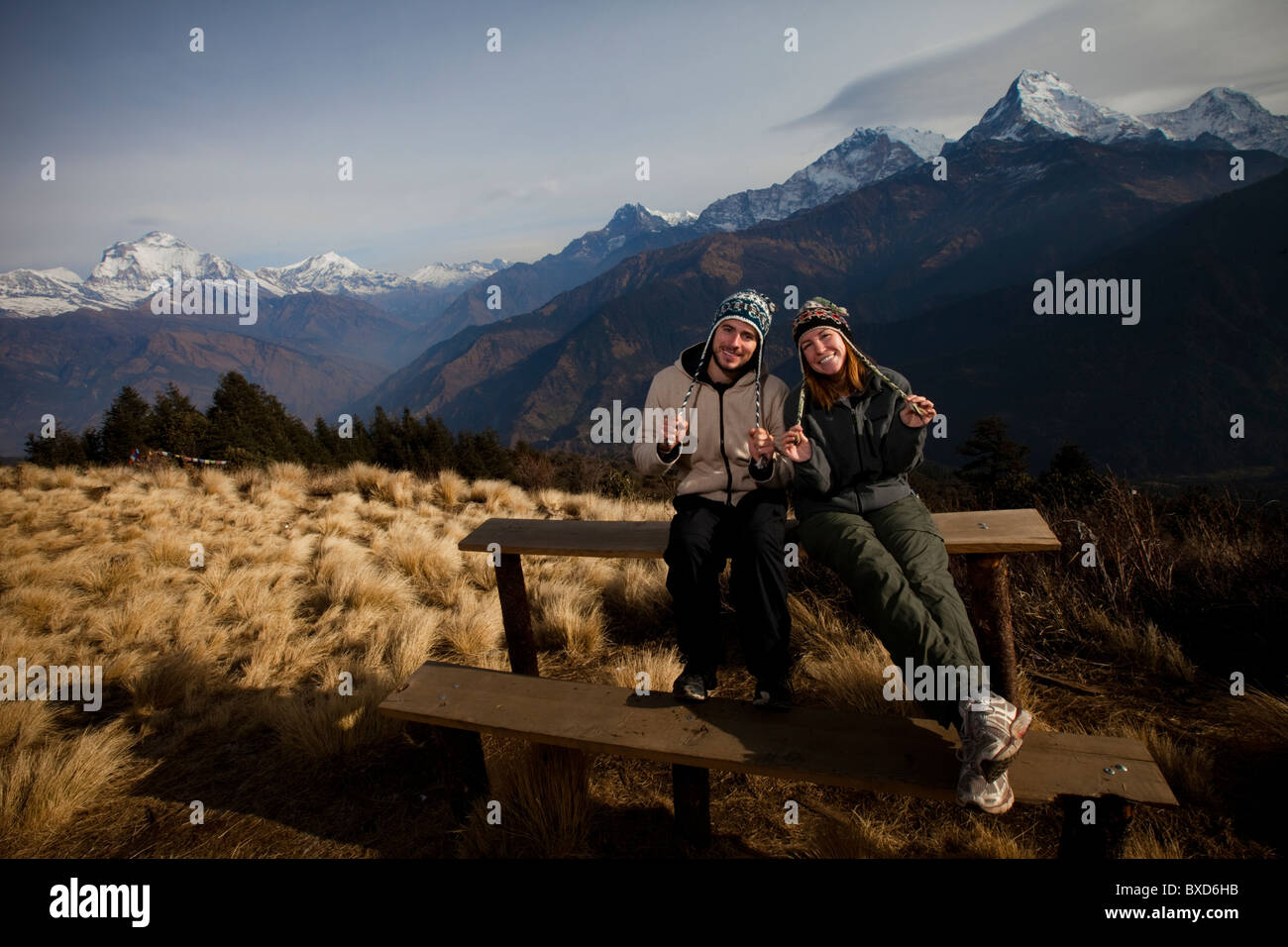 A trekking couple adjust their hats infront of the Annapurna mountain range in Nepal. - Stock Image