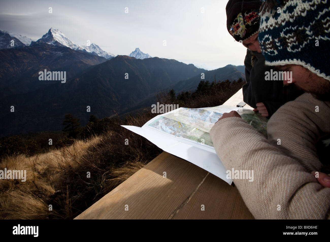 A trekking couple study a map from a viewpoint of Annapurna South in Nepal. - Stock Image