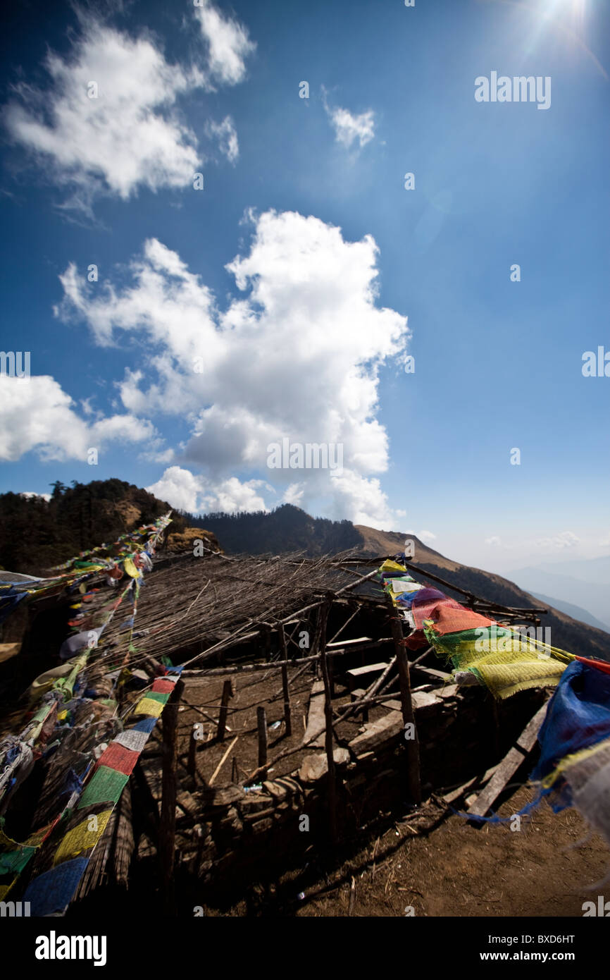 An abandoned teahouse strung with prayer flags in Nepal. - Stock Image