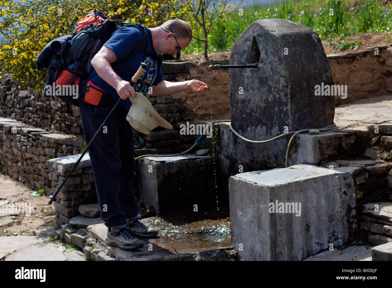 A male trekker stops at a village water fountain to wet his head. - Stock Image