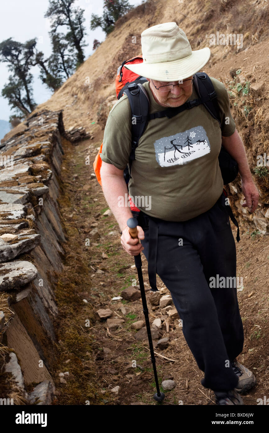 An older male trekker passing a Buddhist prayer wall in Nepal - Stock Image