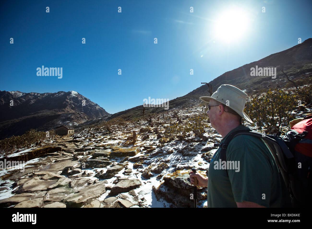 A trekker looks across a high alpine Nepalese pass under the hot sun. Stock Photo