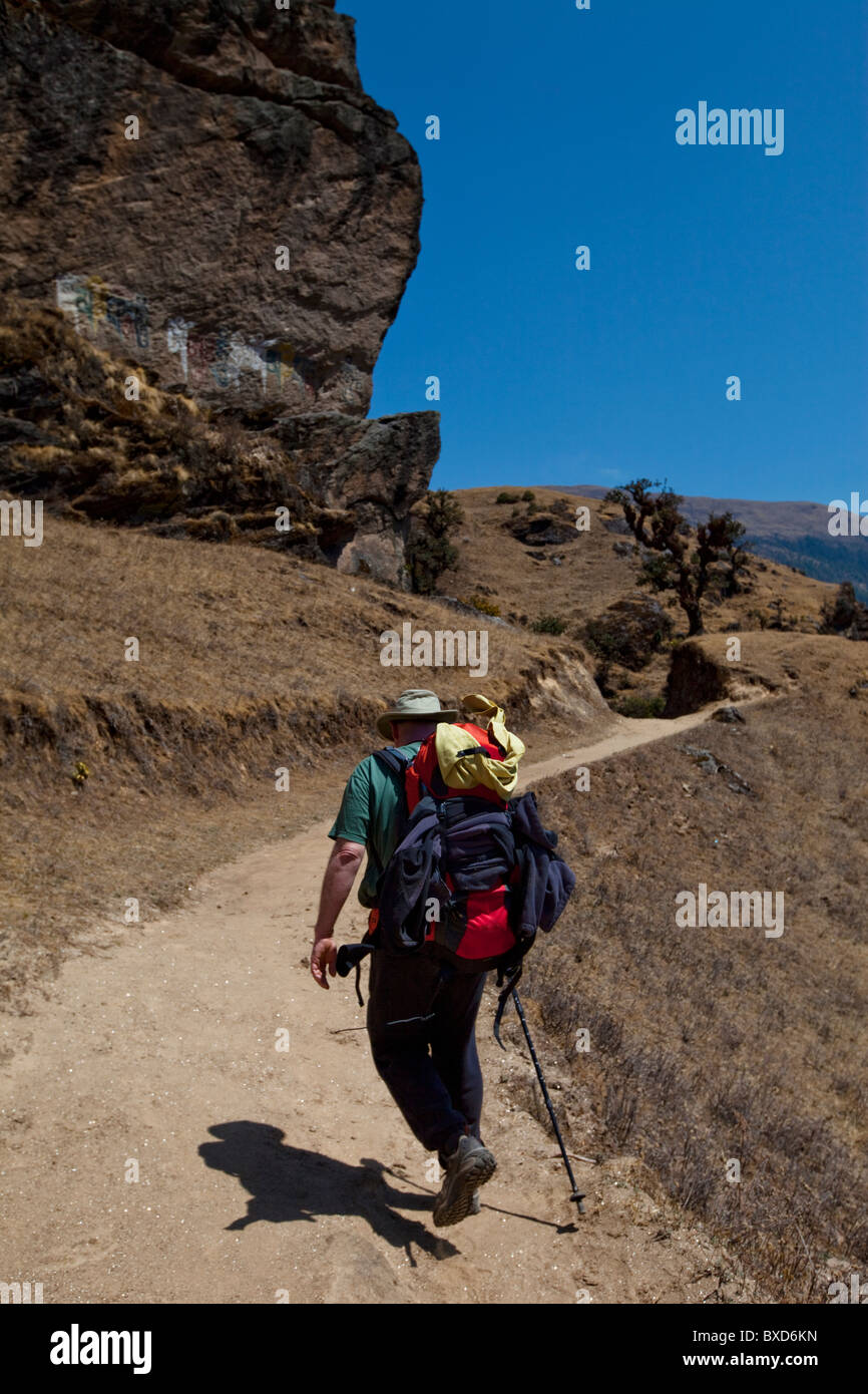 A trekker follows a trade trail past a rock bluff decorated with Buddhist script. - Stock Image
