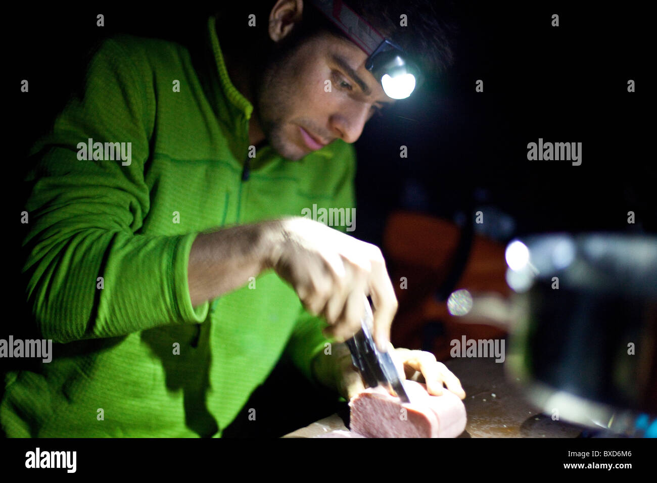 A man cuts up portions of meat for dinner in Three Rivers, California. - Stock Image