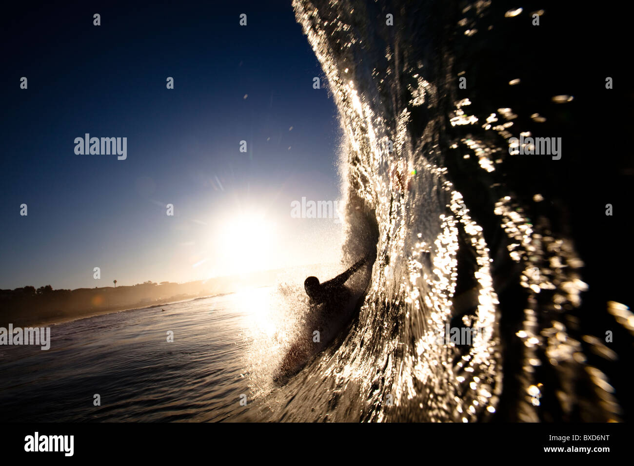 A male surfer pulls into a barrel at Zuma beach in Malibu, California. - Stock Image