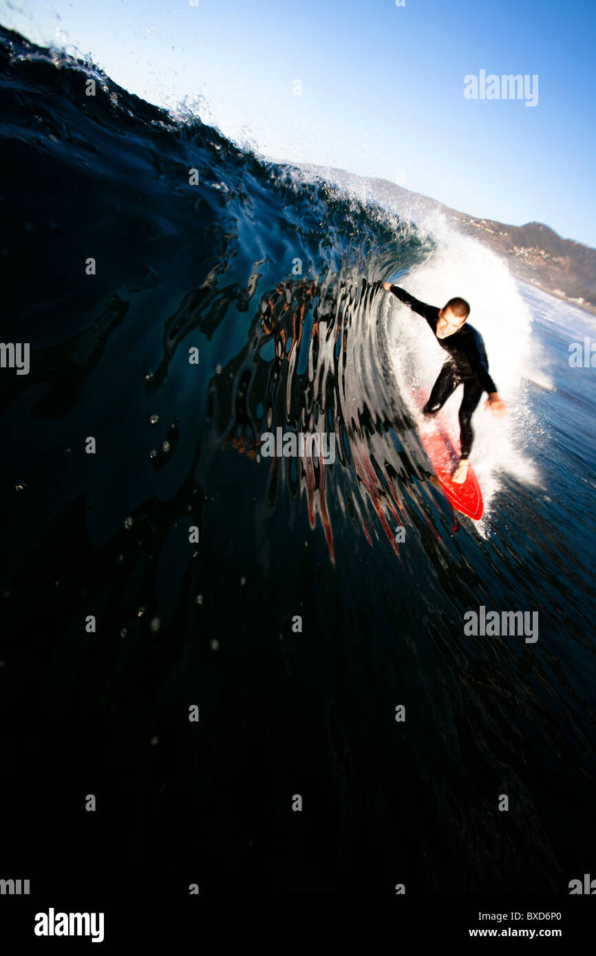 A male surfer pulls into a barrel at Zuma beach in Malibu, California. - Stock Image