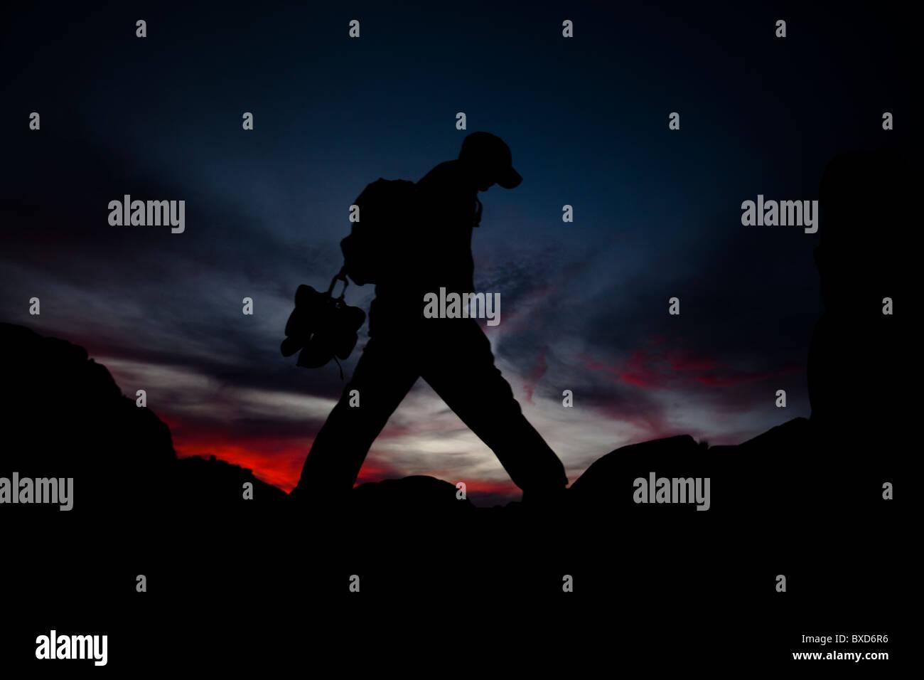 A man hikes in Joshua Tree, California. - Stock Image
