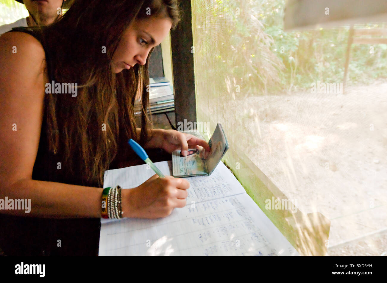 A young woman signs a logbook using her passport in the amazon rainforest. - Stock Image