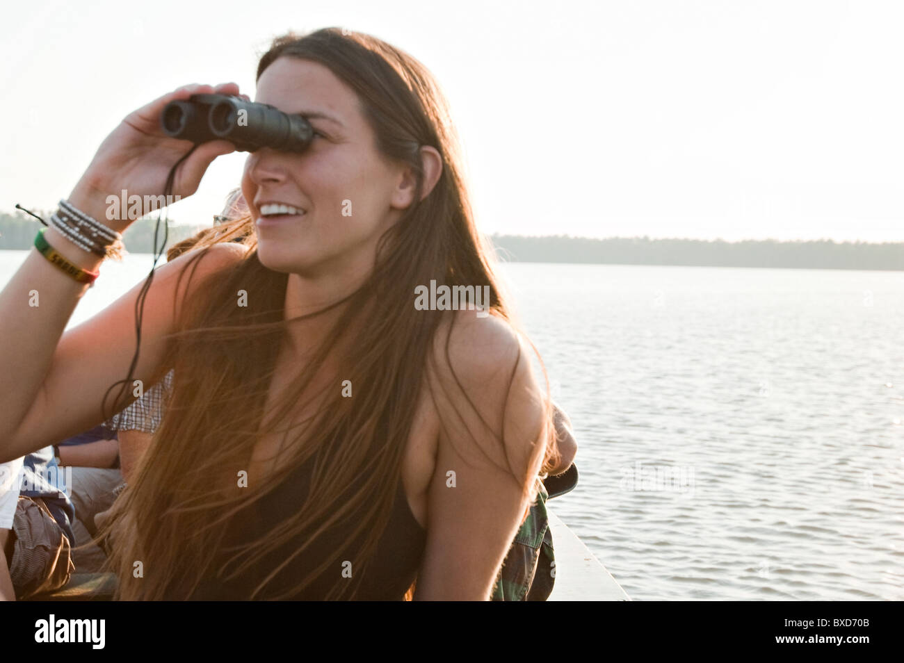 A young woman looks through binoculars at various types of birds on lake Sandoval in the amazon rainforest. - Stock Image