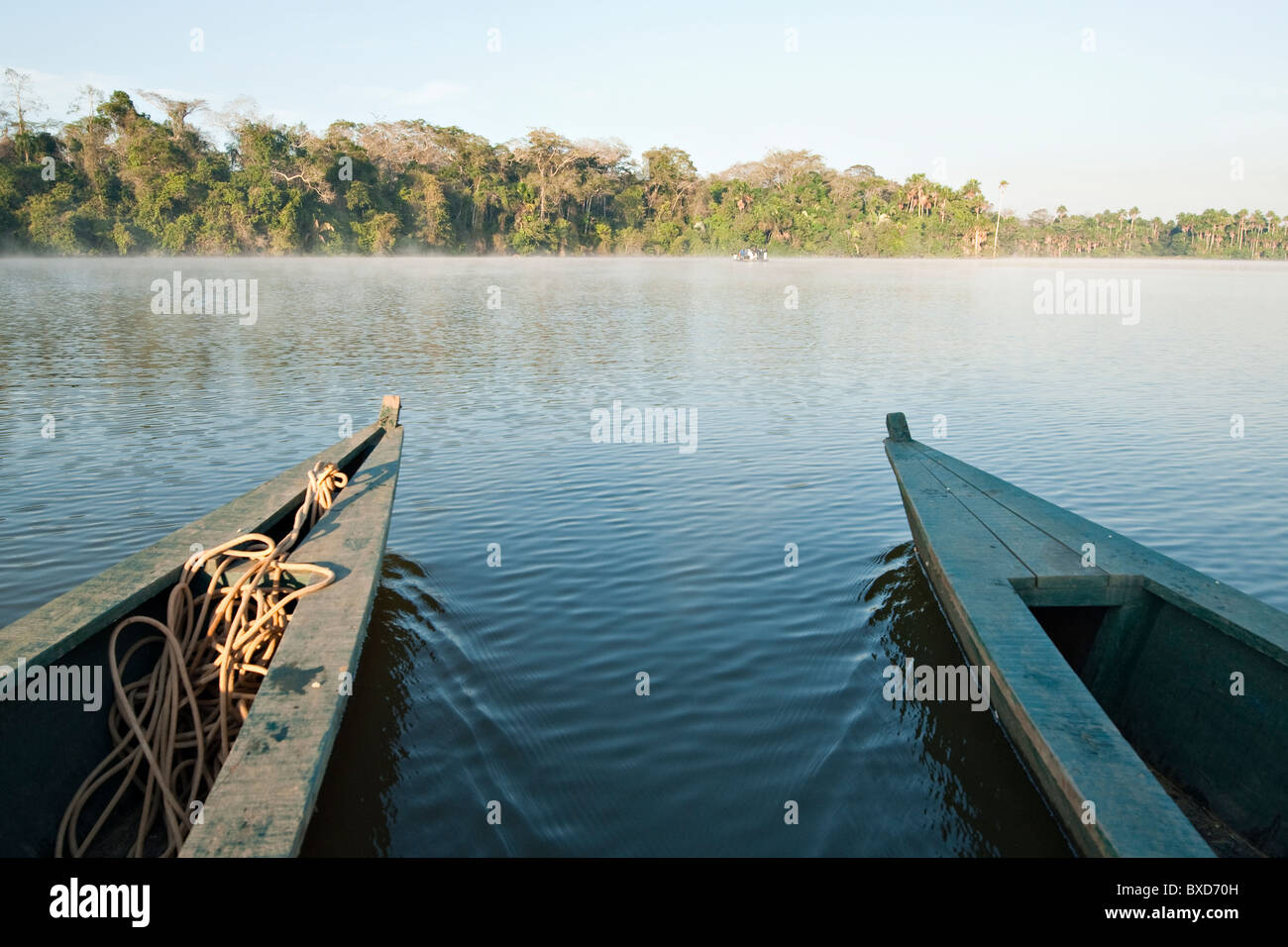 A wooden canoe made of Eucylptus tree floats in the amazon river and connecting tributary rivers in the rainforest. - Stock Image