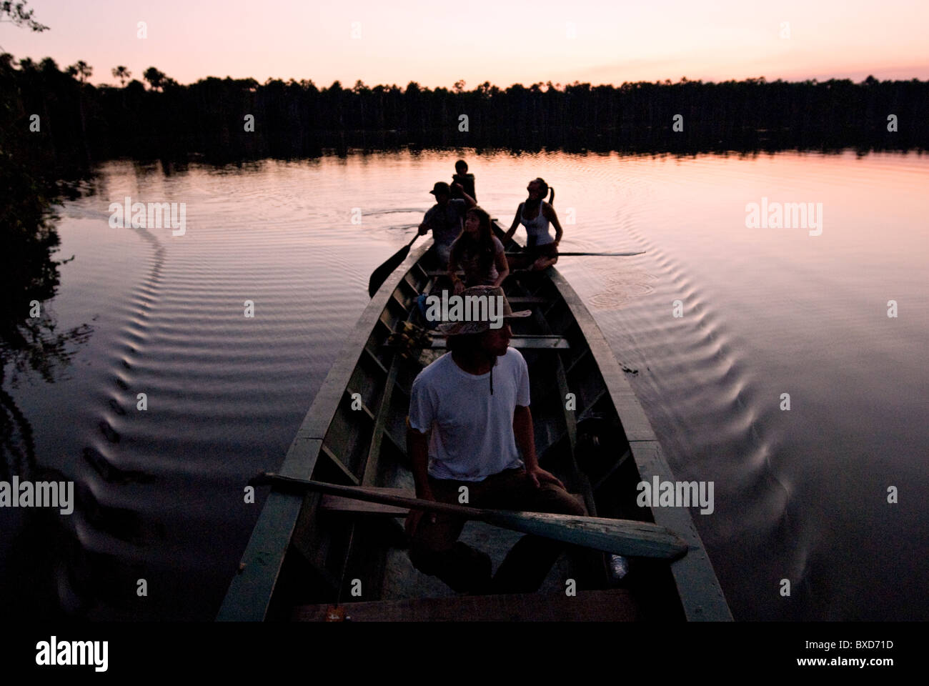 A group of young people paddling a canoe and having fun on lake sandoval at sunset. - Stock Image