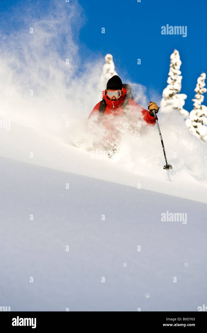 A man skiing deep powder on a sunny day. - Stock Image
