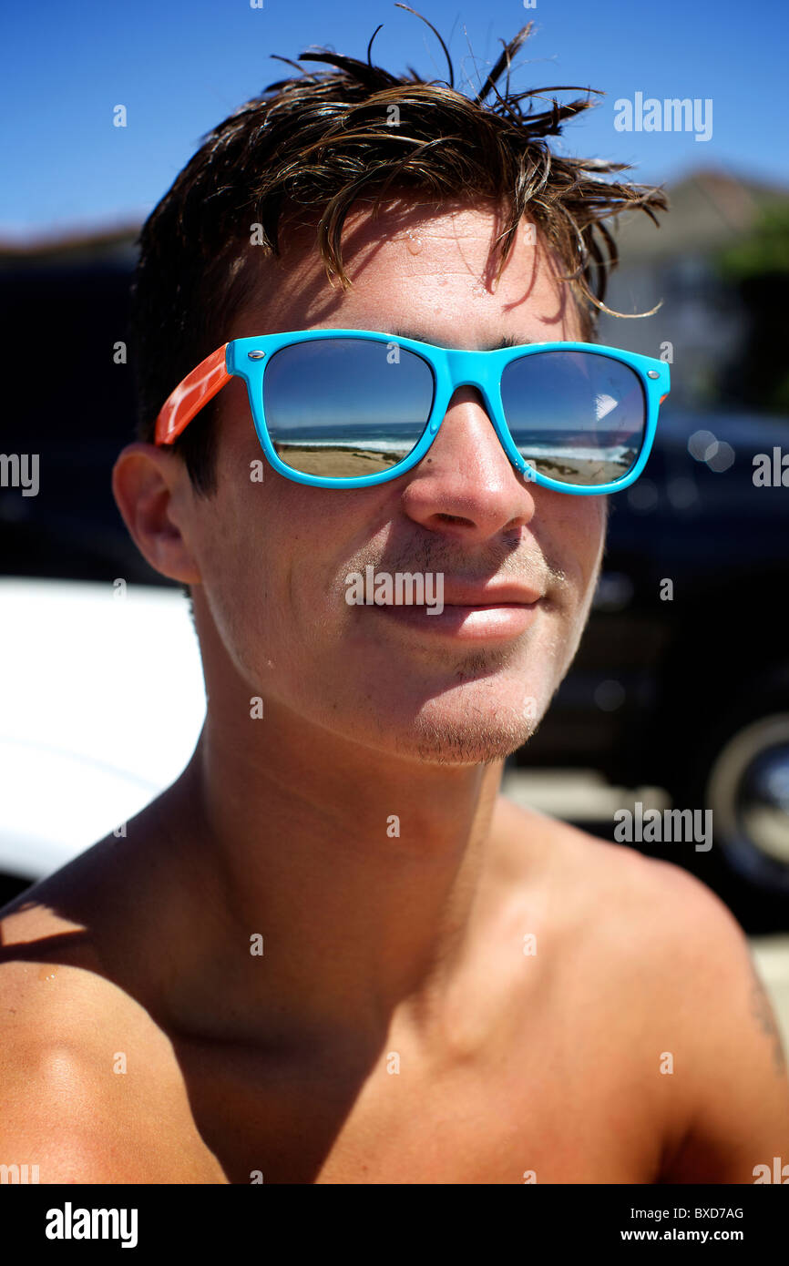 Portrait of male surfer wearing colorful sunglasses. - Stock Image