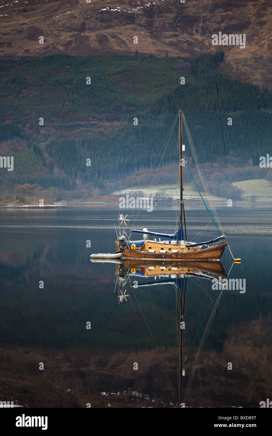 Wooden Sail Boat On Loch Lomond Scotland With Mirror Reflection in Water And Mountains in The Background - Stock Image