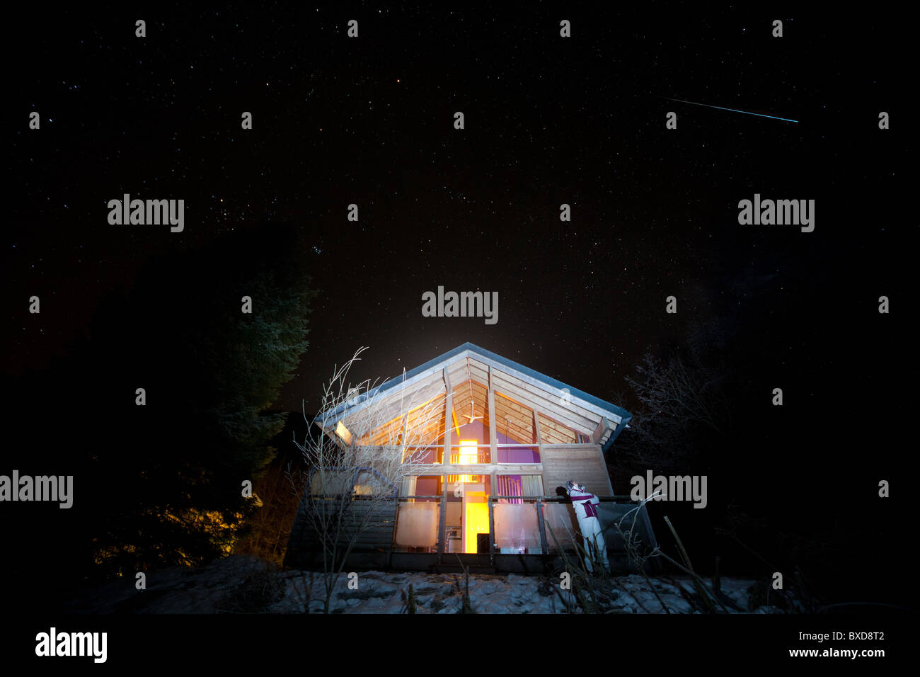 Meteor (Shooting Star) - Over Log Cabin In Scotland On a Dark Night With Star Filled Sky - Stock Image
