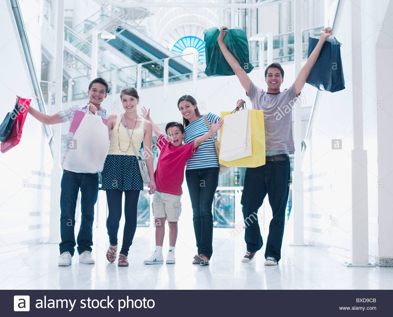 Happy family shopping together in mall - Stock Image