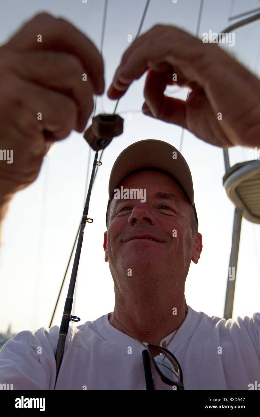 Fisherman ties weights onto his fishing rod - Stock Image