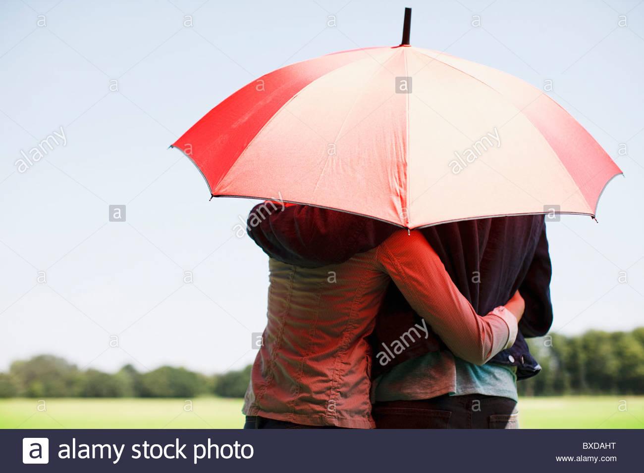 Couple hugging underneath red umbrella - Stock Image