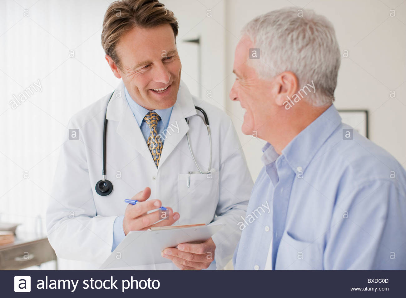 Doctor talking with patient in doctor's office - Stock Image