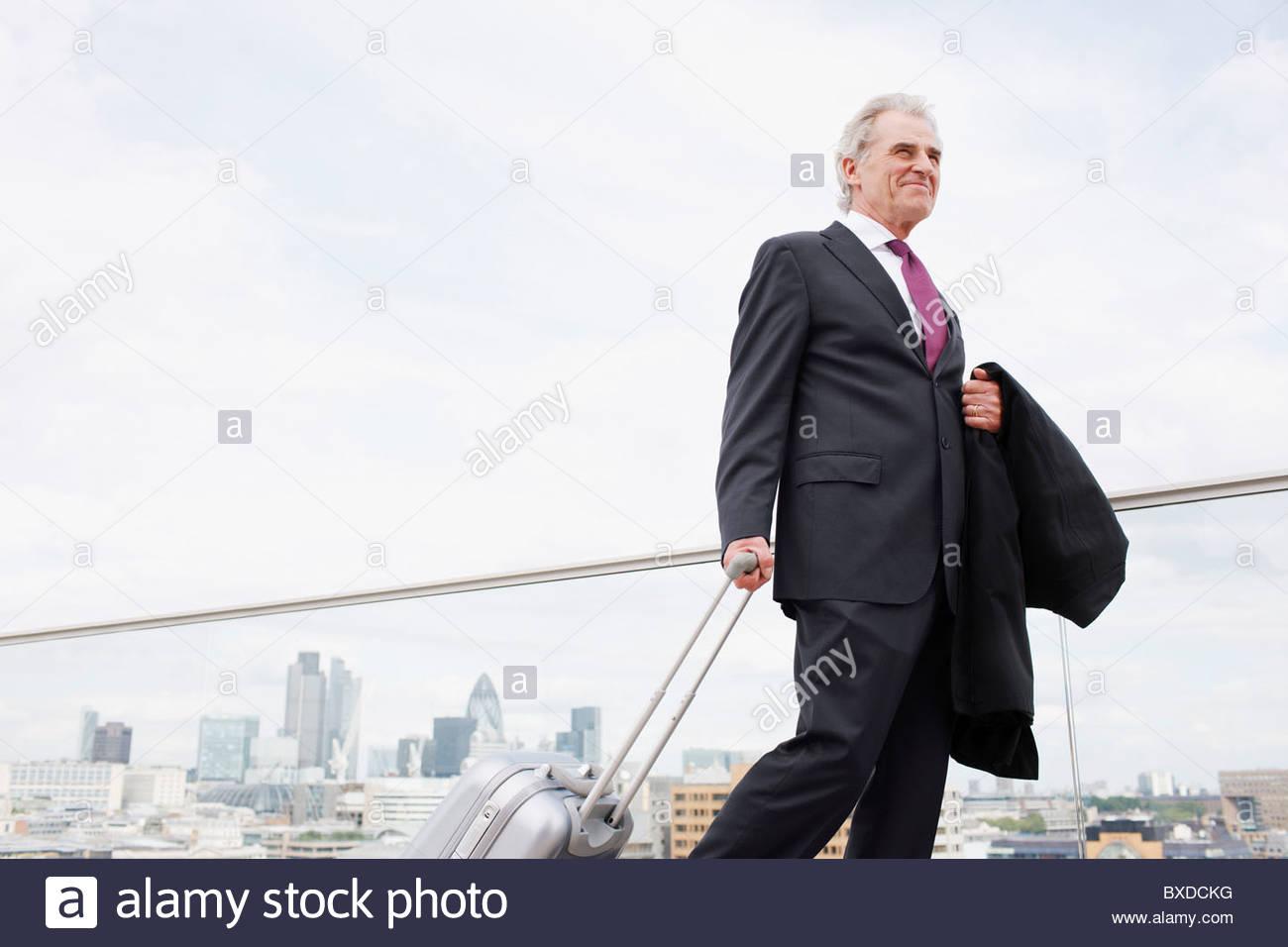 Businessman pulling luggage across urban balcony - Stock Image