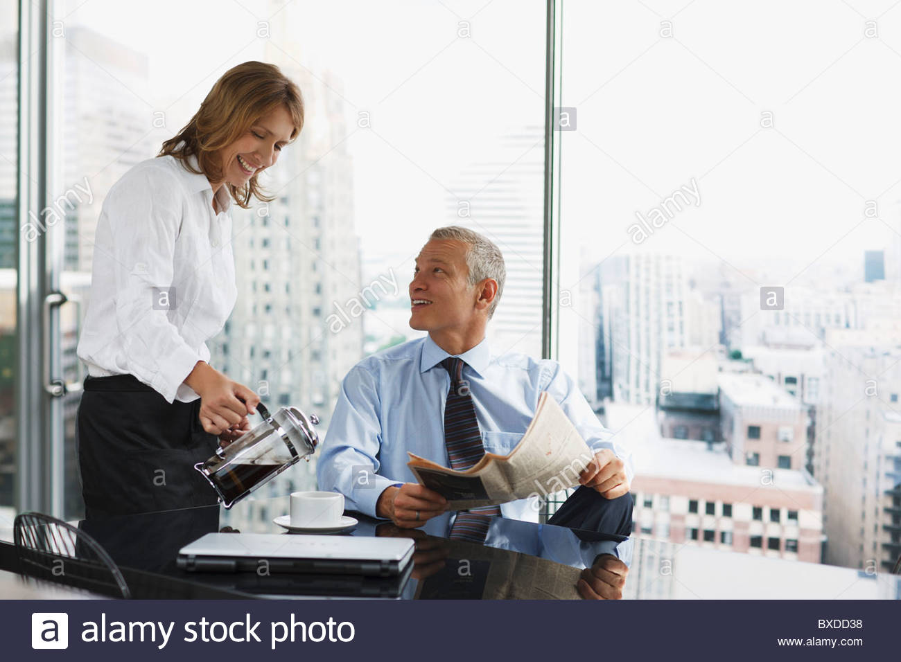 Businesswoman serving co-worker coffee in office - Stock Image