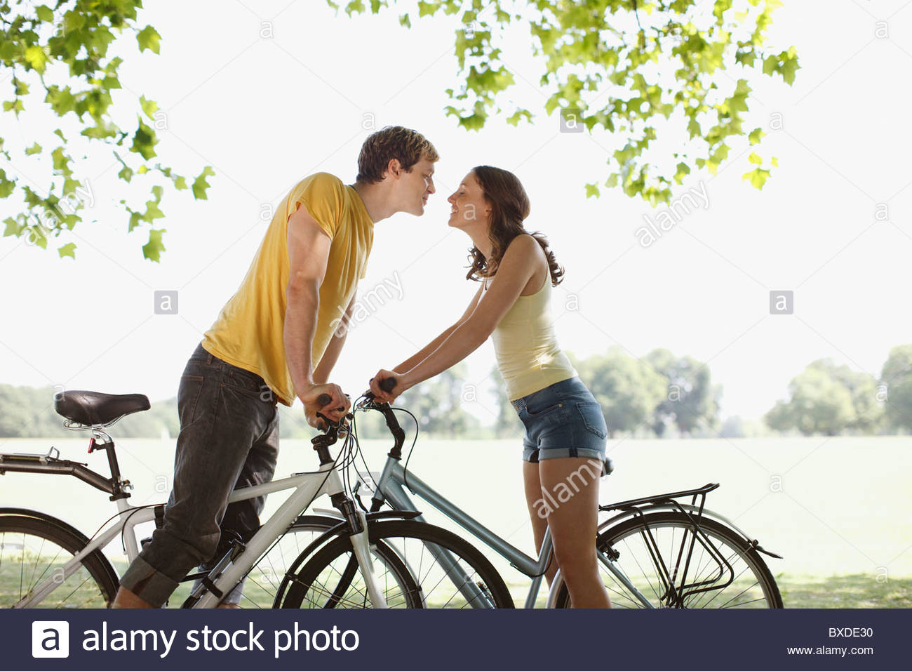 Couple on bicycle stopping and kissing - Stock Image