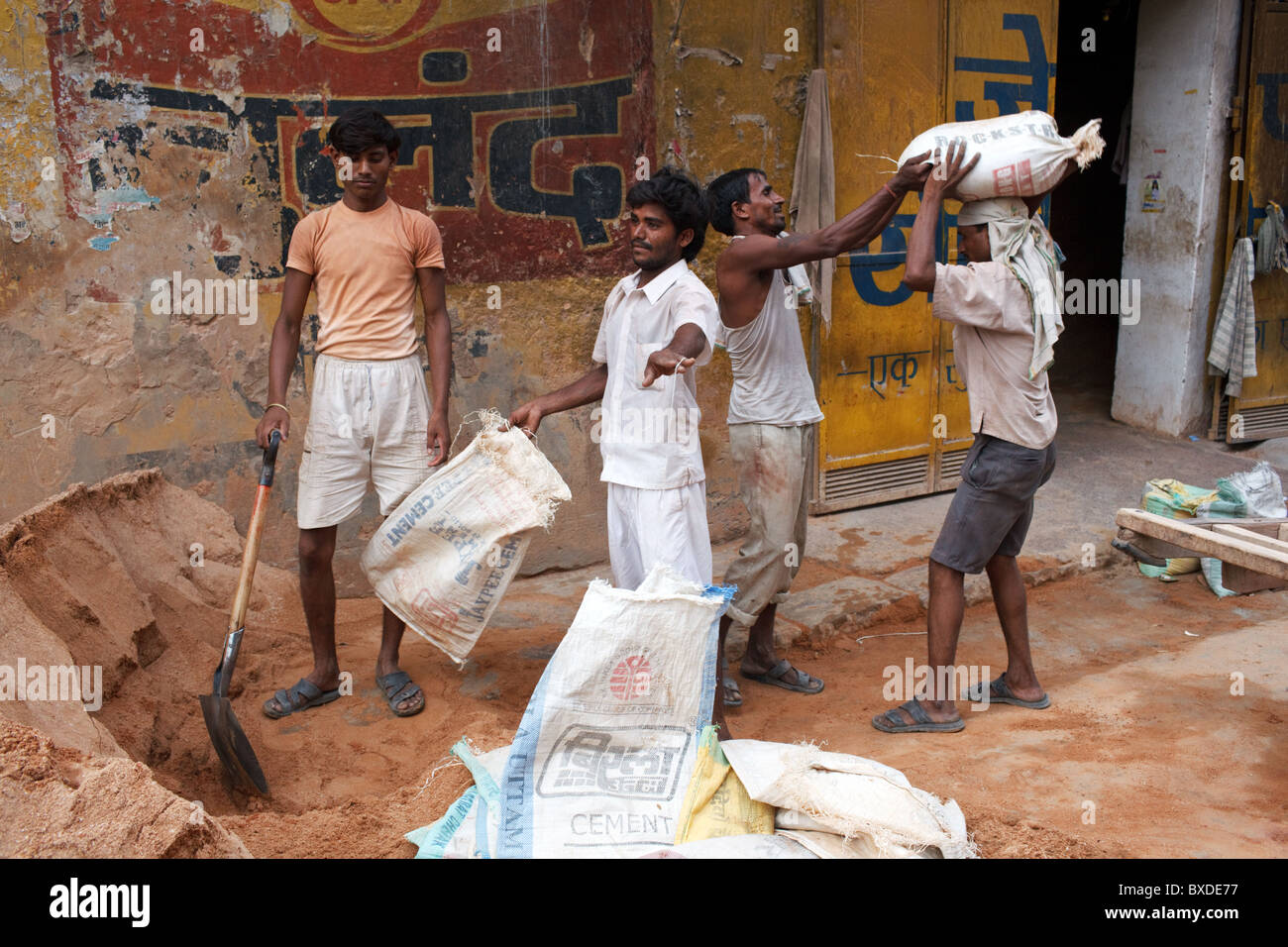 Men do a physical work loading sand into sacks in Old Delhi, capital of India. - Stock Image