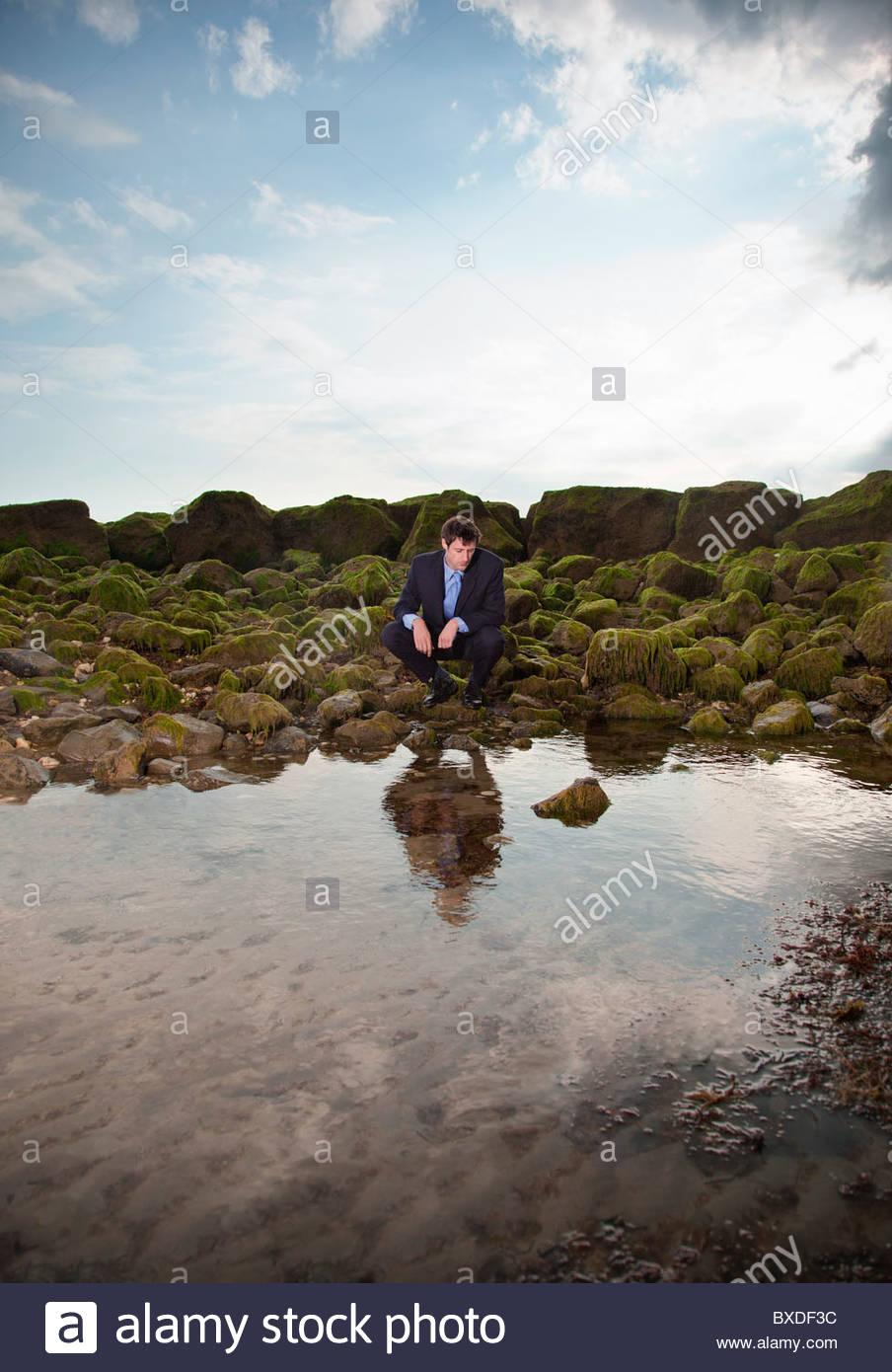 Businessman squatting near ocean tide pool - Stock Image