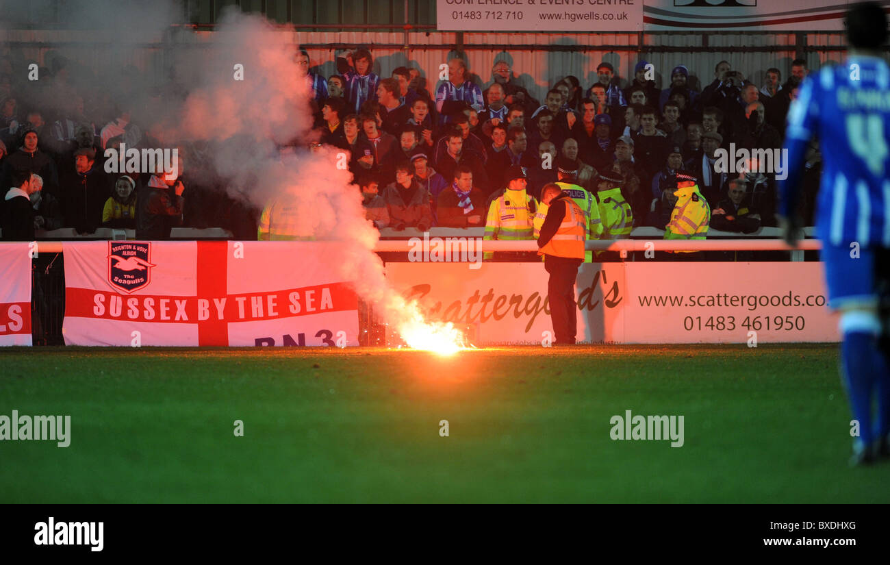 Woking football club, stewards rush over to the away fans after one of them lets off a flare after the match finished - Stock Image