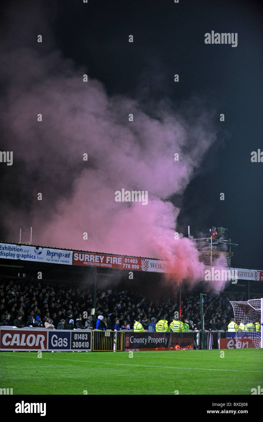 Woking football club, red smoke rises from inside one of the stands after a fan let of a flare just before kick - Stock Image