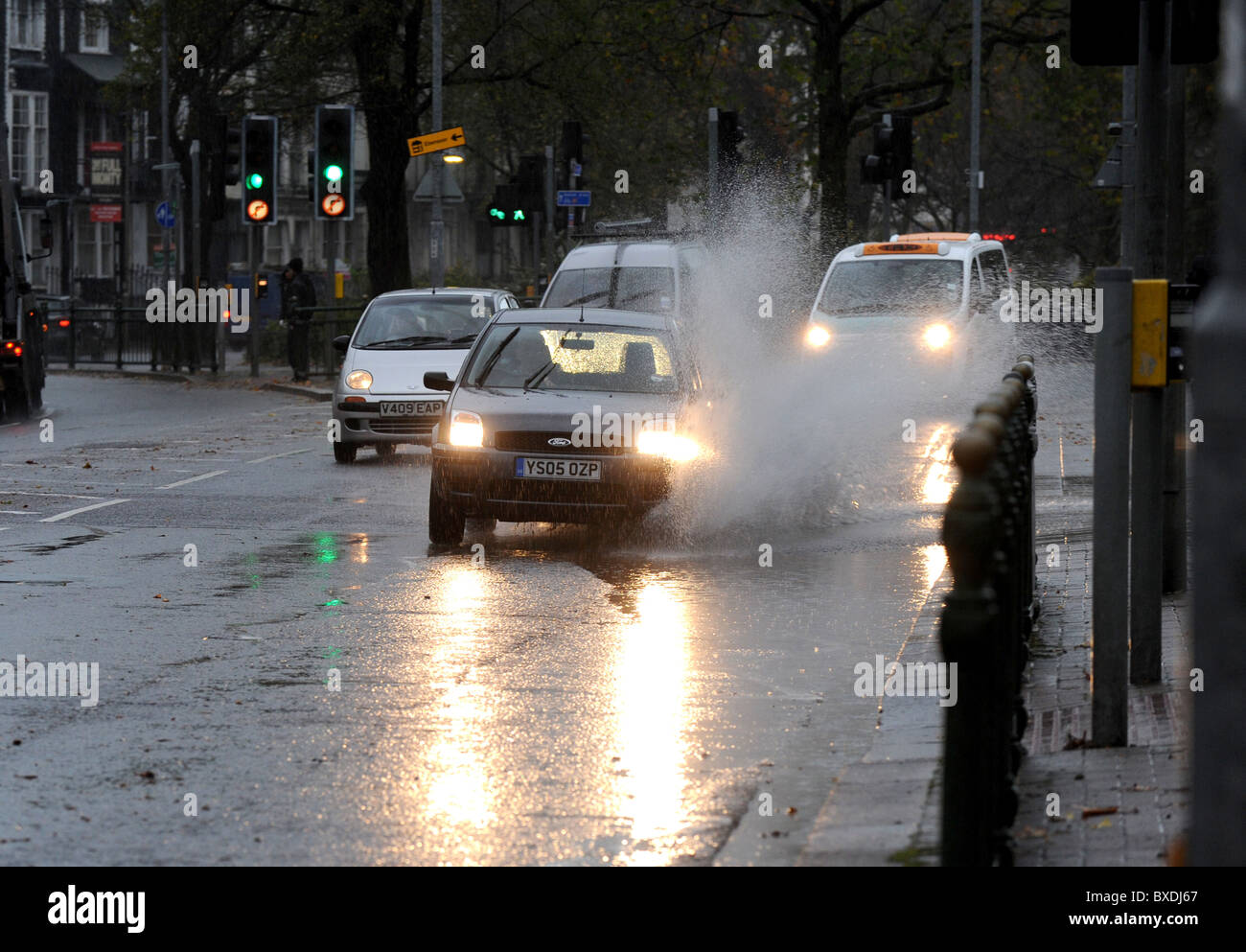 Cars drive through deep puddles on Brighton's Lewes road after deluge of heavy rain - Stock Image