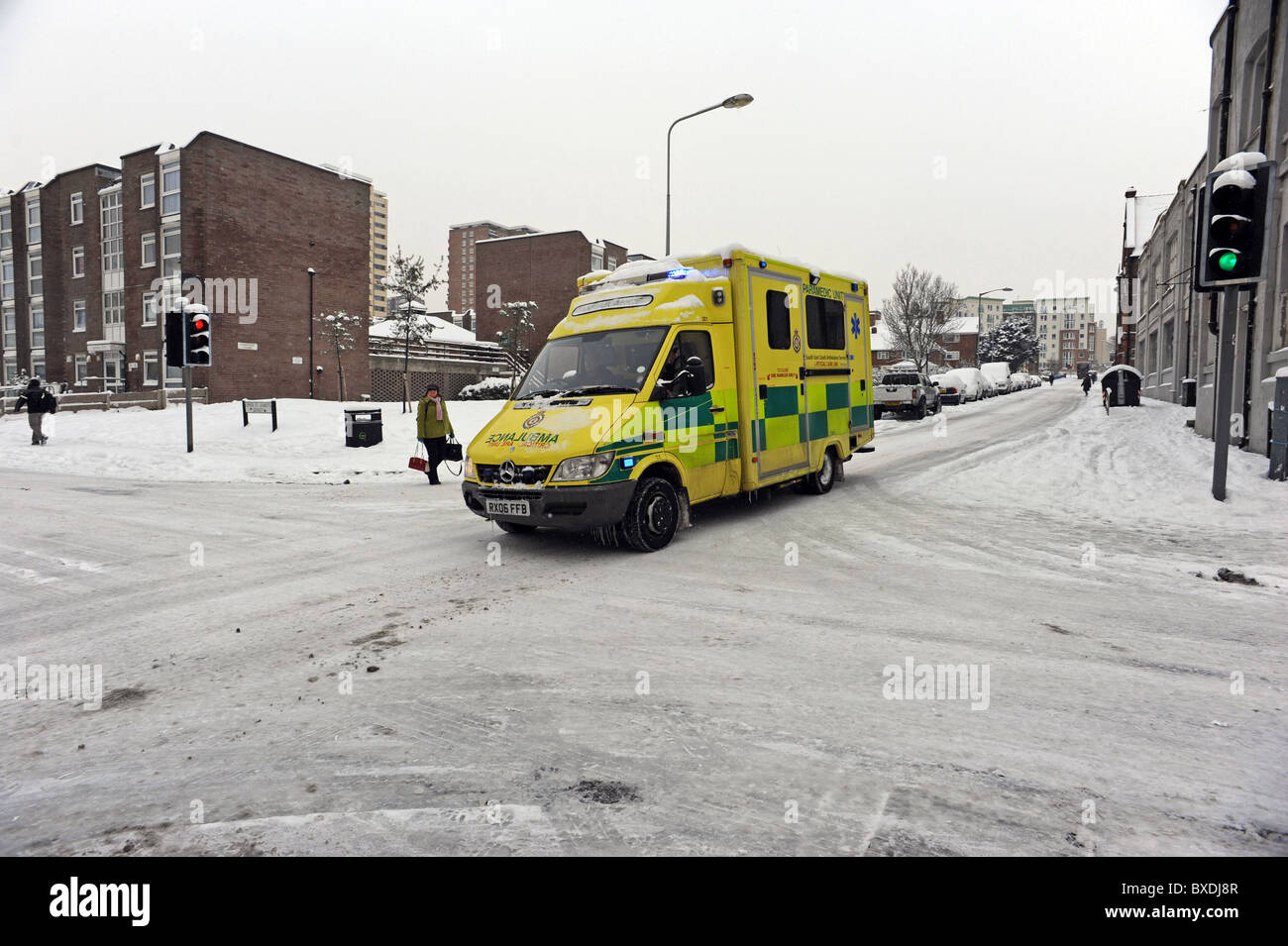 An Ambulance in Brighton travels carefully over the icy roads to answer an emergency call - Stock Image