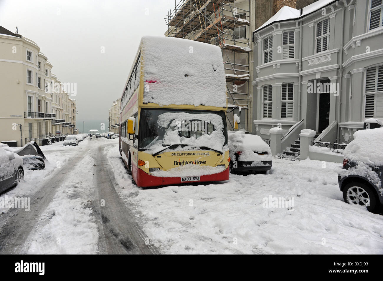 After heavy snowfall an abandoned bus sits in the middle of a normally busy road in Brighton - Stock Image