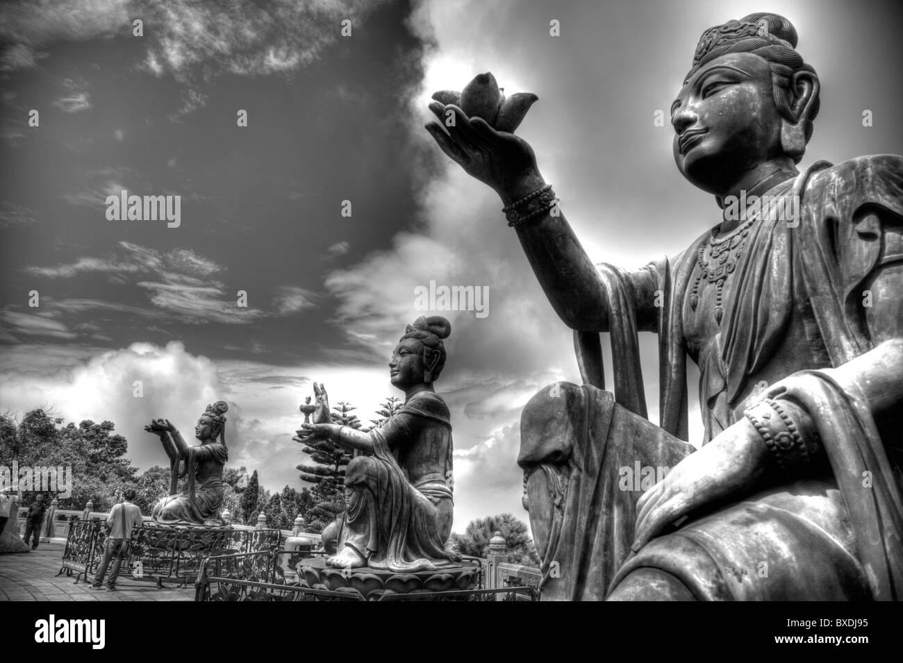 Hong Kong, Lantau island seated bronze statues making offerings to  Buddha, - Stock Image