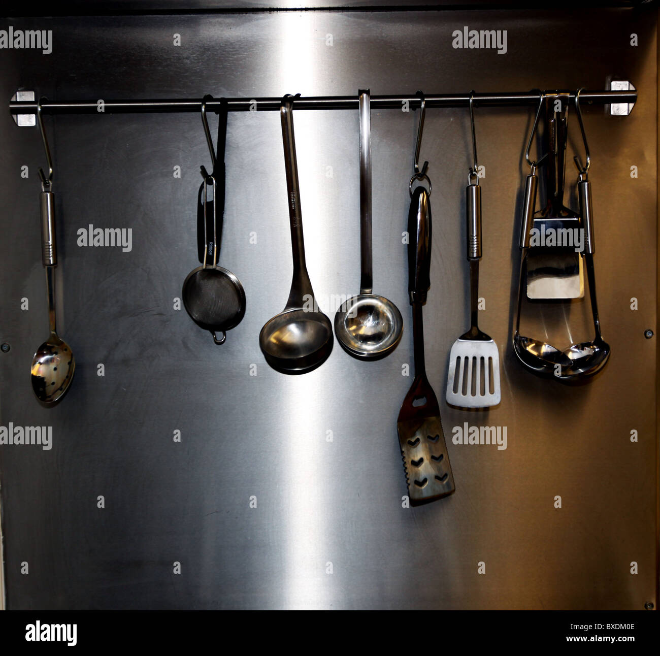 Cooking utensils hanging on rail in commercial kitchen Stock Photo
