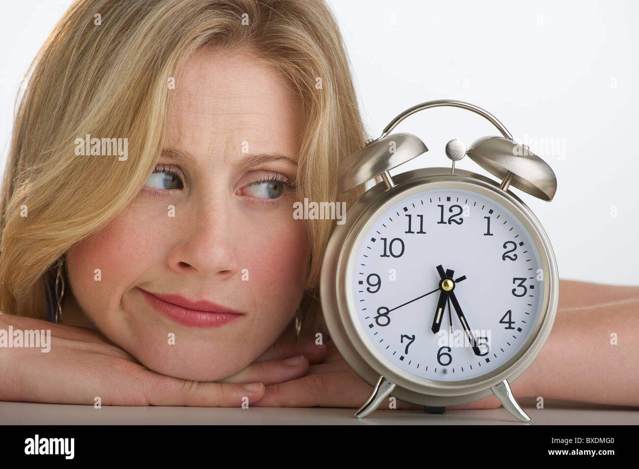Worried blond woman looking at alarm clock - Stock Image